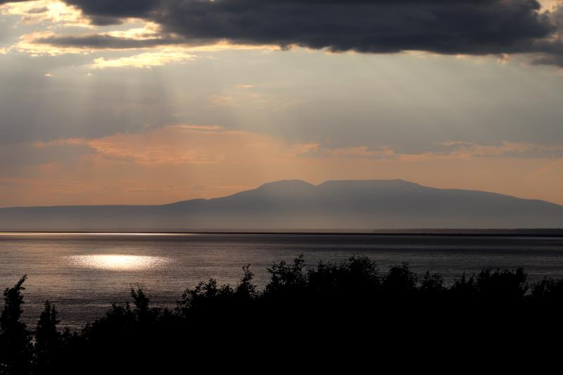 Sunlight peaking through clouds with Mount Susitna in background