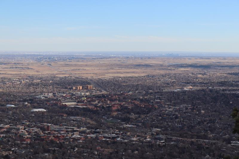 View of Boulder at summit of Mt. Sanitas with Denver in distance