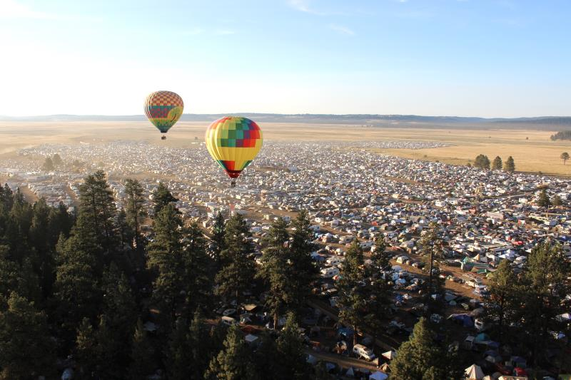 Two hot air balloons hovering over festival near camping area with trees nearby