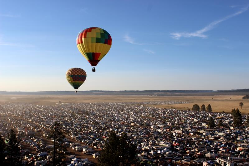 Hot air balloons hovering over festival camping area