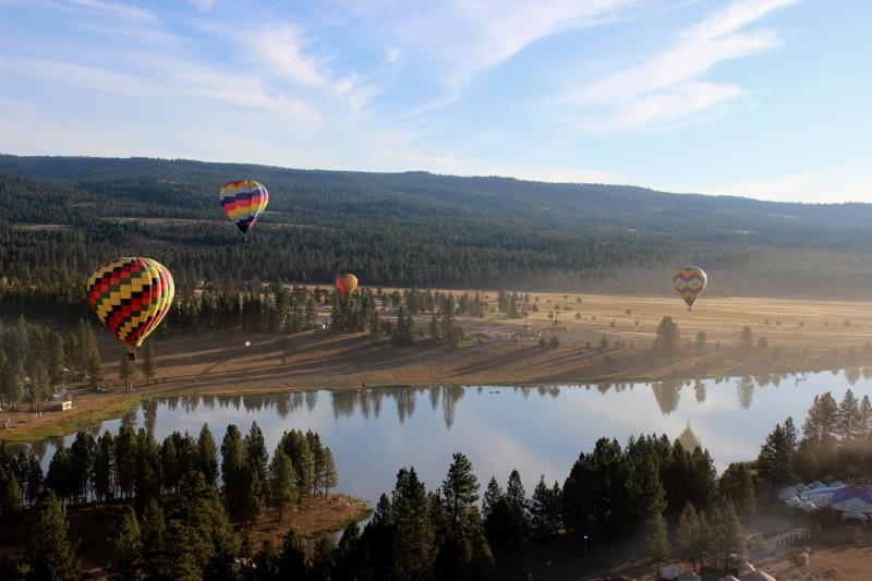 Four hot air balloons hovering near lake at festival