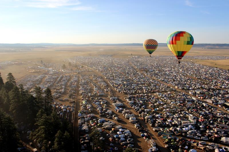 Hot air balloons hovering over camping area