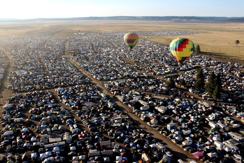 Hot air balloons over festival camping area