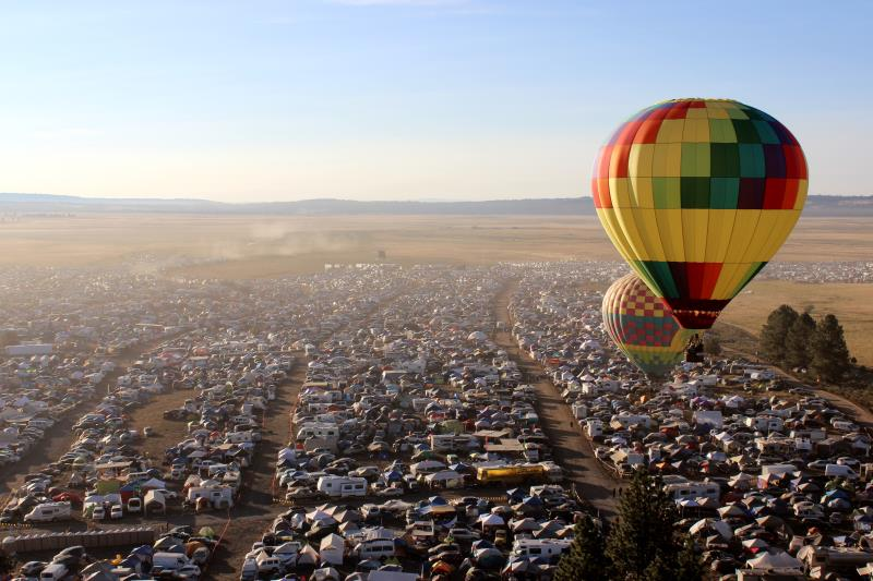 Hot air balloons over camping area near perimeter