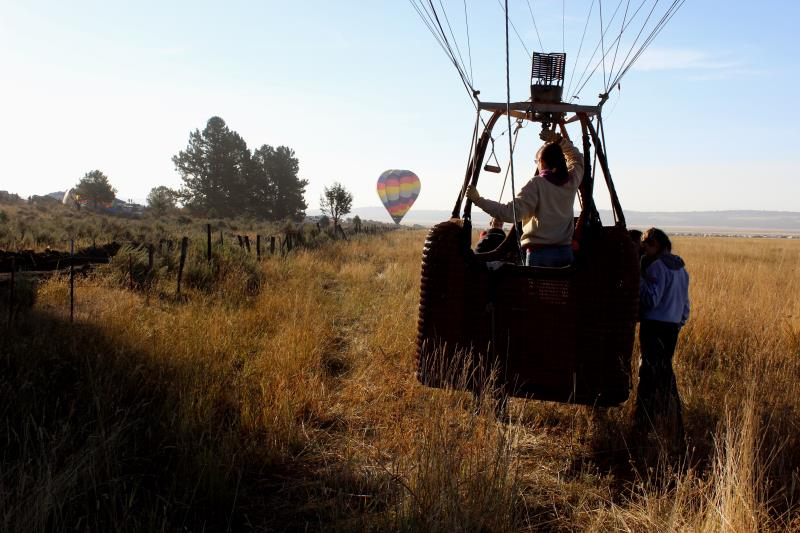 Hot air balloon pilot hovering over ground outside of festival camping area around 8:00AM