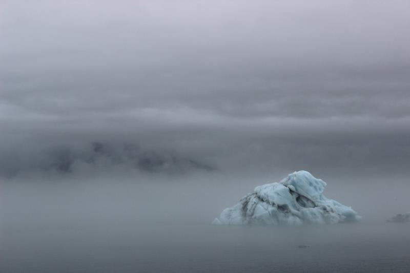 View of iceberg from land with fog covering land in background