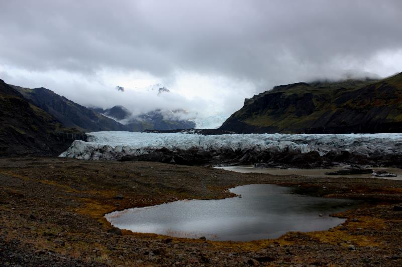 Glacier with clouds, mountains and small pond in front of them