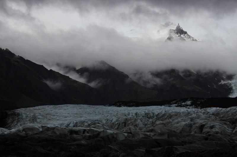 View of glacier with dark clouds and mountains