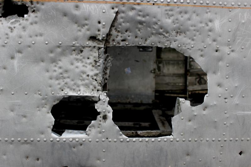 Close up of hole in plane with vandalism of plane